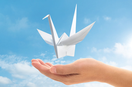 let go: a hand let go origami paper pigeon into the sky
