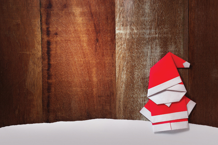 Origami Santa claus paper craft stand wooden background