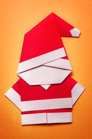 Origami Kerstman papier ambachtelijke op oranje achtergrond Stockfoto
