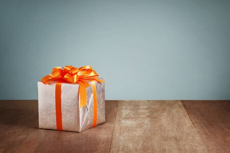 Gift box with orange ribbons on wooden background