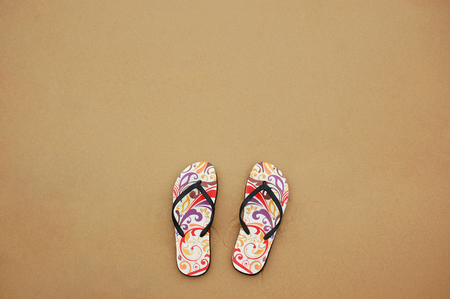 top angle: a pair of slipper on the beach sand. Top angle
