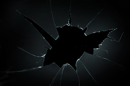 cracked glass: broken cracked glass with big hole over black background Stock Photo