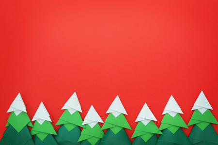 Handmade origami paper craft Christmas tree on red paper