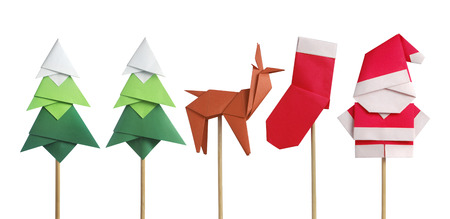 Handmade origami paper craft Santa Claus, green Christmas trees, reindeer and stocking isolated on white Foto de archivo