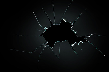 broken cracked glass with big hole over black background Standard-Bild
