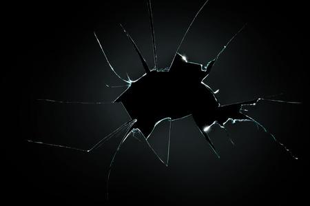 vidrio resquebrajado roto con gran agujero sobre el fondo negro Foto de archivo