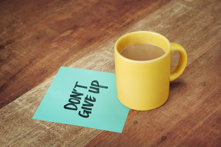 not give: paper with hand writing and coffee mug on wood table
