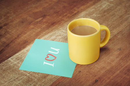 paper with love icon and coffee mug on wood table