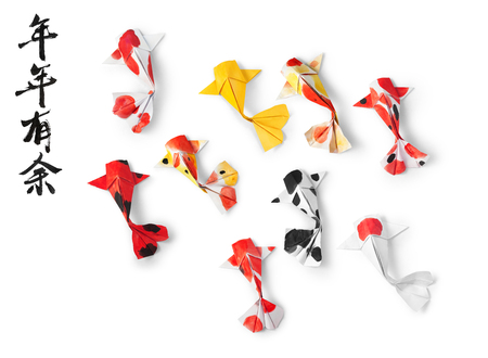 handmade paper craft origami koi carp fish on white background. Translation of text: May you have a prosperous new year.