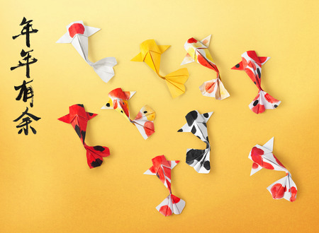 handmade paper craft origami koi carp fish on yellow background. Translation of text: May you have a prosperous new year.