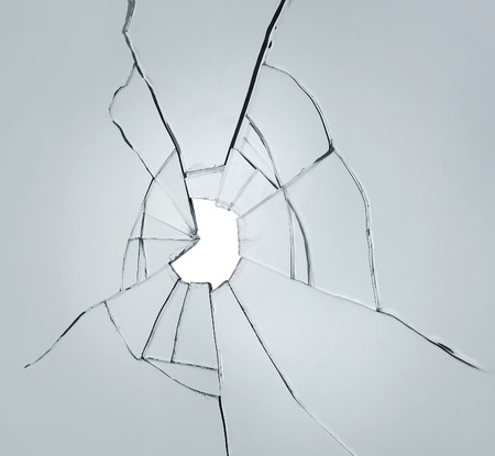 Broken window glass crack splitter on white gray background Standard-Bild