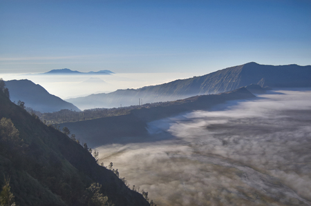Steep black mountain silhouette in front of Fog and cold mist of volcano Bromo in Indonesia