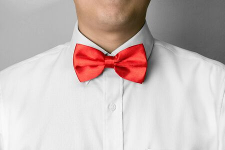 Man ties a red bowtie at the collar