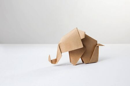 Brown paper origami elephant isolated on white background