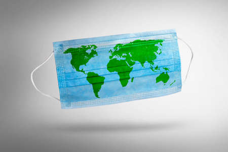 Blue medical disposable face mask with world map. Concept of coronavirus quarantine.