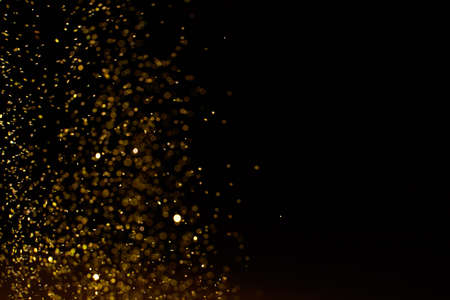 Sparkling golden glittering effect isolated on black background. Standard-Bild