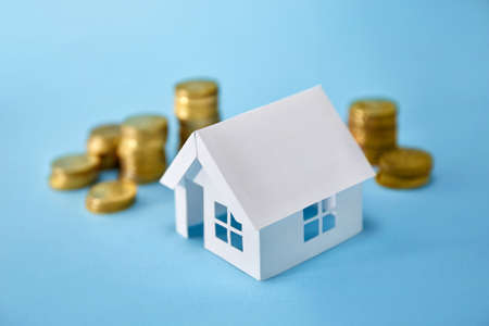 Paper house model and coin money on blue background