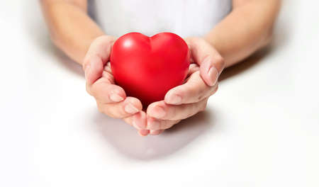 The woman is holding a red heart. Concept for charity, health insurance, love, international cardiology day. Standard-Bild