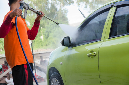 pressured: Closeup Of A Mechanic Washing A Car By Pressured Water At Garage Stock Photo