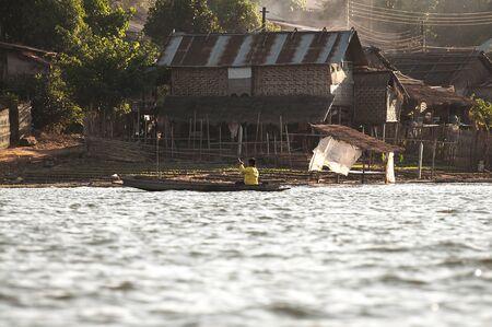 sangkhla buri: Fat boy and old wood boat paddle on river in Sangkhla Buri,Kanchanaburi province, Thailand Stock Photo