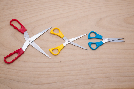 parlance: Three scissors like idiom Big fish eat little fish in the business on wooden texture. Stock Photo