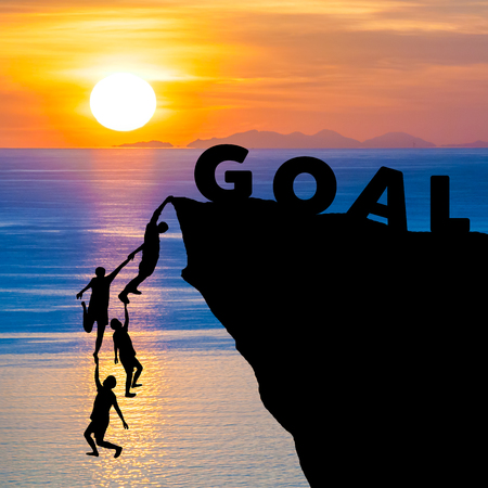 goal setting: Silhouette teamwork of people climbs into cliff to reach the word GOAL with sunrise (goal setting business concept)