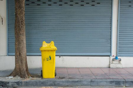 wheelie: large yellow wheelie bin for rubbish, recycling and garden waste. old trash bin in thailand foot path pavement.