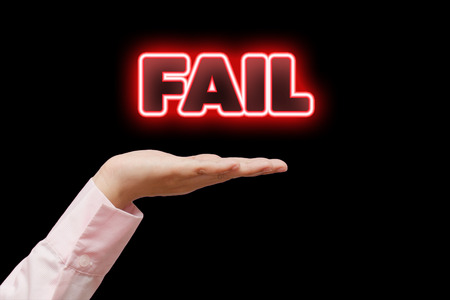 unaccepted: Business woman hand cupped holding the word FAIL with red neon light