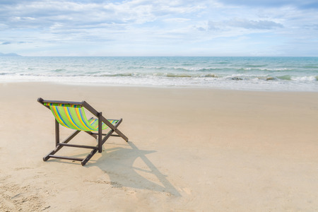fresh concept: Beach chair on the sand with summer, Summer background. Summer fresh concept. Lonely in summer beach. Selective focus on chair. Stock Photo