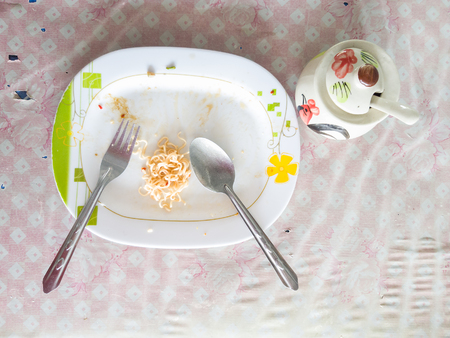 leftovers: Plate of spaghetti noodle at the end of a meal on a table Stock Photo