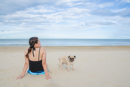 Beautiful asian girl with blonde hair in a black blouse sitting on the beach with a cute dog puppy pug