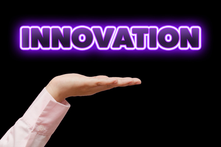newness: Business woman hand cupped holding the word INNOVATION with violet neon light Stock Photo