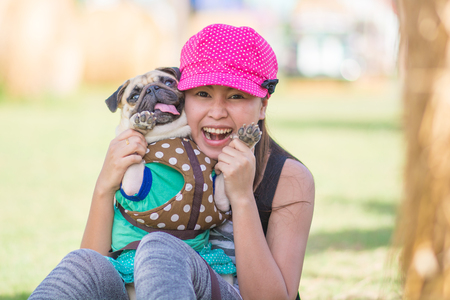 Portrait of a asian teenage woman girl hug and play with her cute dog puppy pug outdoors on fields