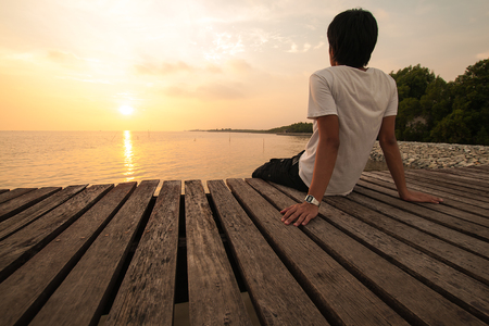 solitude: Young man relax siting on pier looks forward with sunset sky