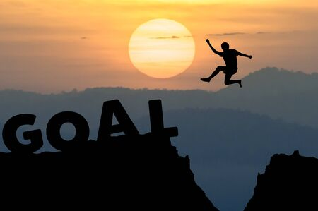 goal setting: Silhouette man jumps to the word GOAL with sunrise.(Business goal setting concept) Stock Photo