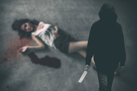 murderer: Murderer hooded man ready to attack to kill his victim that is the woman to died on ground. (Criminal concept)