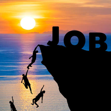 candid: Silhouette of people climbs into cliff to reach the word JOB with sunrise (find job recruitment concept)