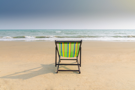 idling: Beach chair and shadow on the white sand beach with sunset light sky (lonely concept)