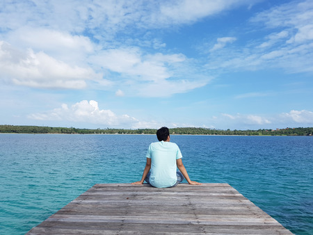 A young traveler man sit on the wooden bridge in summer sea beach bay and enjoy the beauty of seascape. Imagens - 61192082