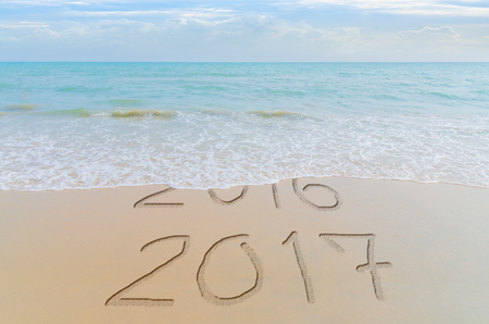 replace: Happy New Year 2017 replace 2016 concept on the summer sea beach. New Year 2017 is coming concept. Stock Photo