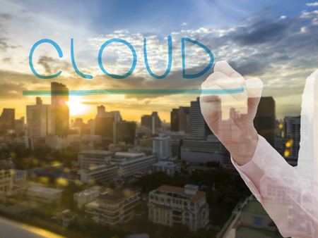 thru: Businesswoman hand write the word cloud thru window glass with city background for cloud computing concept Stock Photo