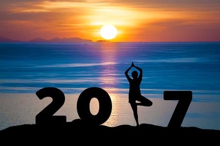 simbolo de la mujer: Joven de la silueta de la yoga juego de la mujer en el mar y 2017 años, mientras que la celebración de feliz año nuevo