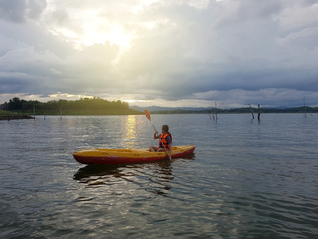A female kayaker paddles across a lake against sunset in cloudy and stormy day