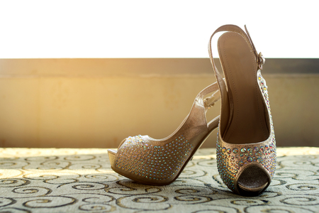 Wedding Shoes for bride in gold theme on sofa and window in background with sun light Stock Photo