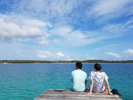Two man sitting together on pier of wooden bridge in the sea and looking forward