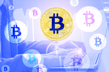 Business man looks at the laptop, to trade or investment and checking the rate of digital currency bitcoin. (Trading cryptocurrency concept)