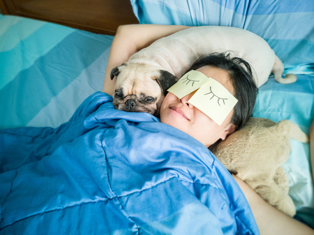 Handsome woman resting and sleeping rest with her pug dog annoy on bed in the bedroom. Pet and owner funny concept. Lonely woman and her best friend.