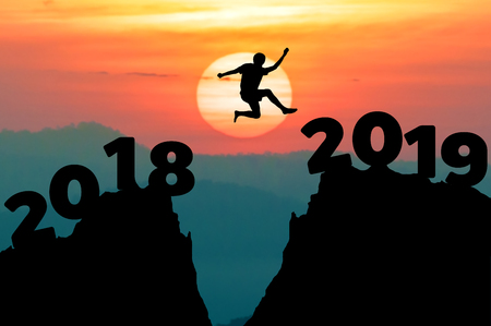 Man jump between 2018 and 2019 years. Happy new year 2019 concept for achievement.
