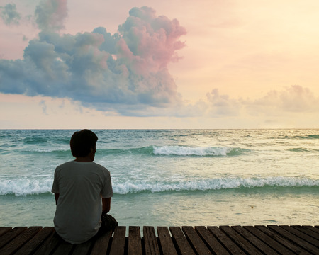 Sad man sitting by the sea. Concept about people, sadness and loneliness