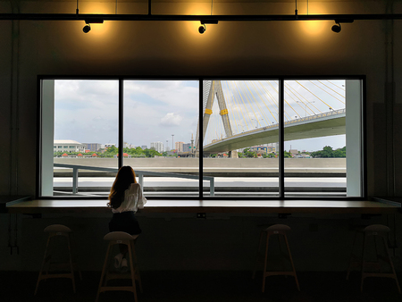 Young slim beautiful girl sits on a high bar stool in a cafe with stunning panoramic views of Bangkok. Siesta break with a cup of fragrant cappuccino Reklamní fotografie